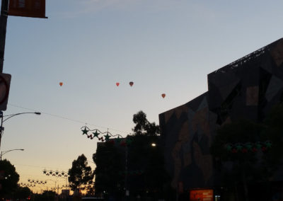 Many hot air balloons above Melbourne city